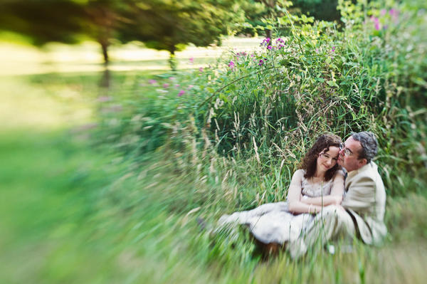 bride and groom sitting in the grass