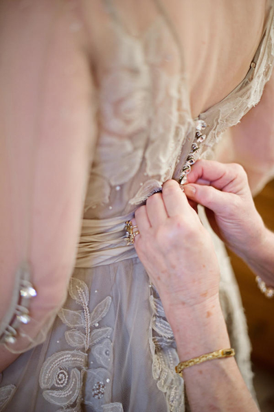 mother doing up bride's buttons