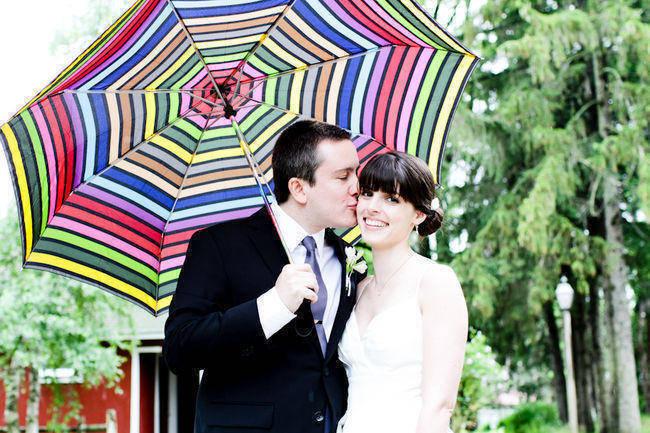 bride and groom under striped umbrella