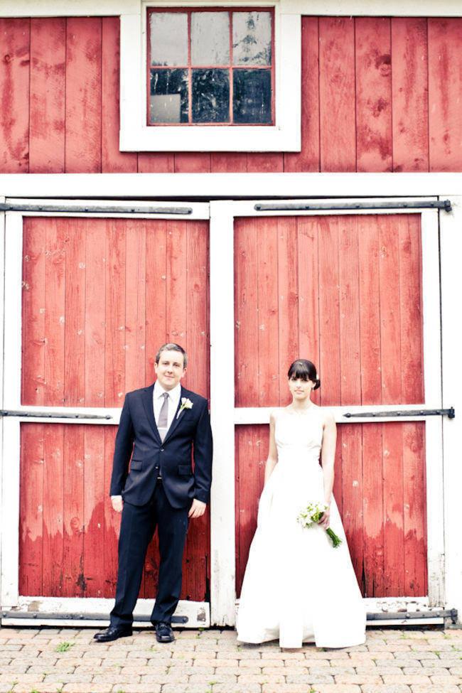 bride and groom in front of red barn doors