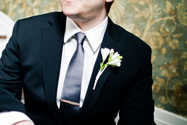 groom in black suit and black tie