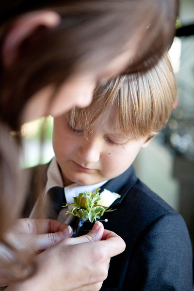 bride pinning boutonniere on her son