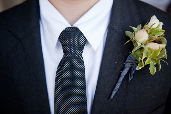 white rosebud boutonniere and polka dot tie