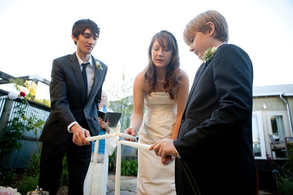 bride, groom, and groom's son lighting unity candle