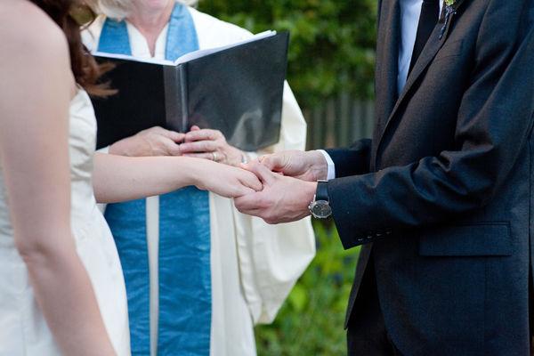 groom placing ring on bride's finger