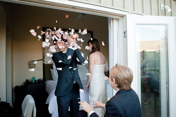 son tossing rose petals at the groom