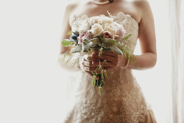 bride holding white and dusty pink bouquet