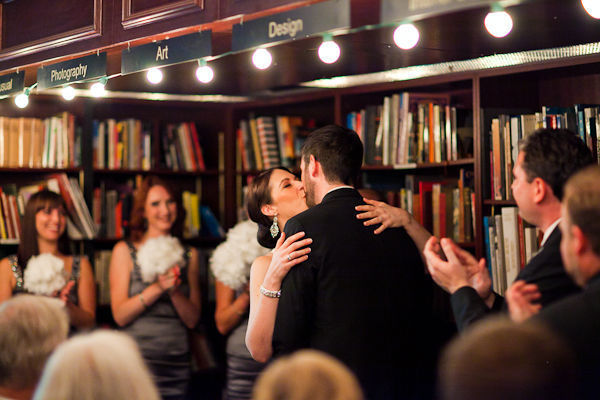 bride and groom first kiss in book store