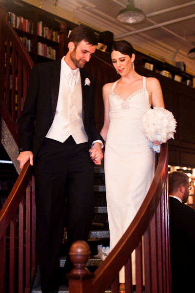 bride and groom walking down book store stairs