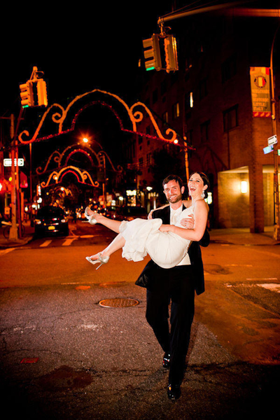 groom carrying bride down street