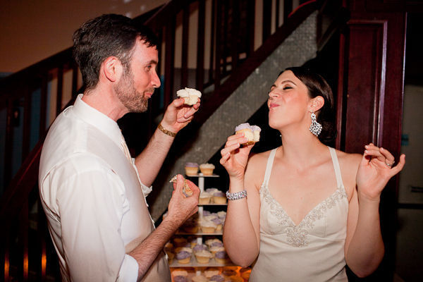 bride and groom eating cupcakes