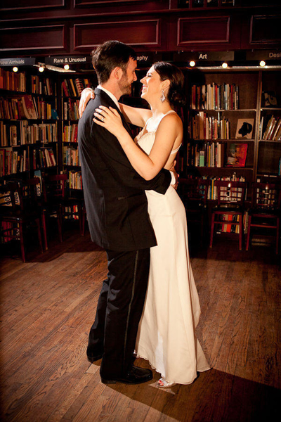bride and groom dancing in bookshop