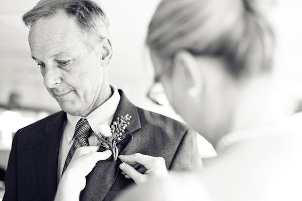 boutonniere being pinned on father of the bride