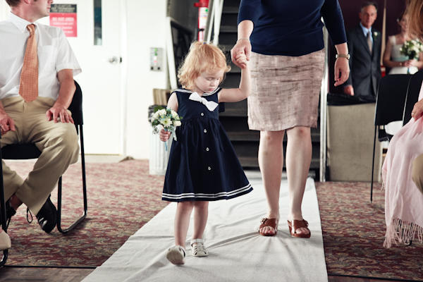 flower girl in sailor dress walking down the aisle