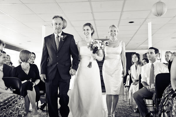 bride being walked down the aisle by her father and mother