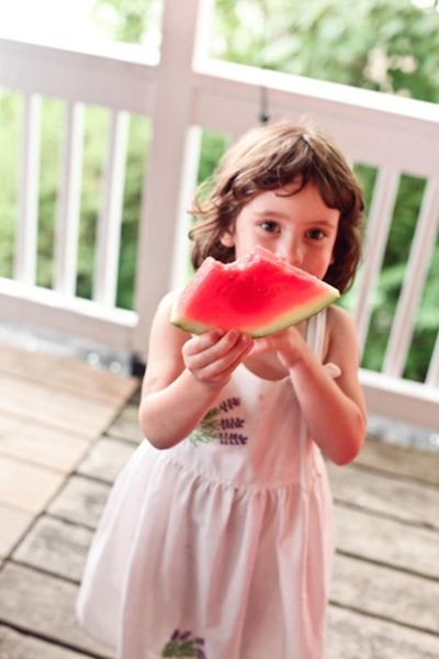 young wedding guest eating watermelon