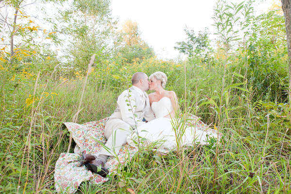 bride and groom kissing on a blanket in a field