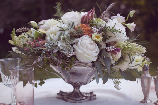 rustic rose centerpiece in antique silver vase