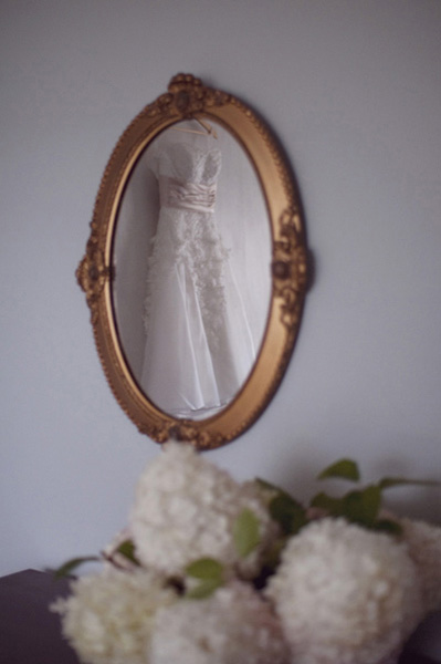 vintage wedding dress reflected in antique mirror