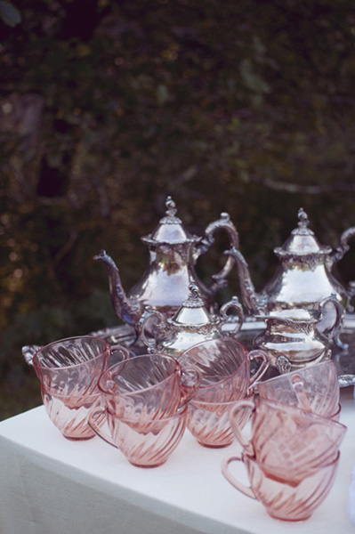 pink depression glass tea cups and silver tea pots