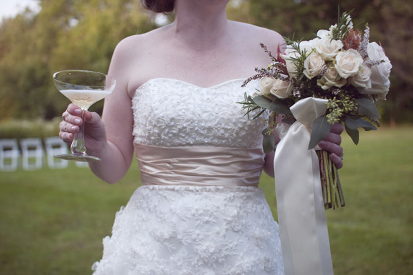 bride with champagne and rustic bouquet