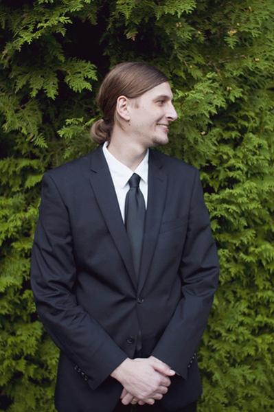 ponytailed groom in black suit