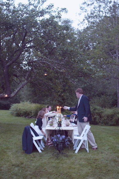 lighting candles at outdoor wedding reception