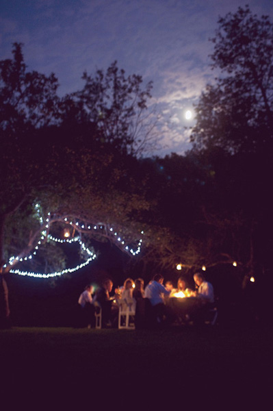 outdoor wedding reception lit by twinkle lights