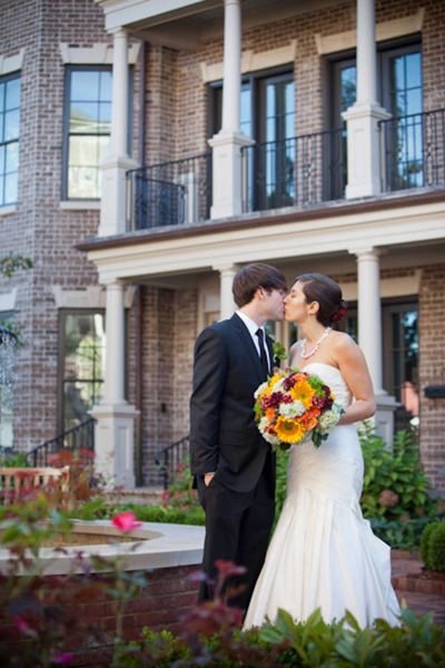 bride and groom kissing in front of brownstone