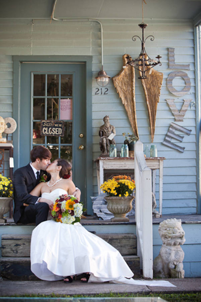 bride and groom kissing on antique store steps