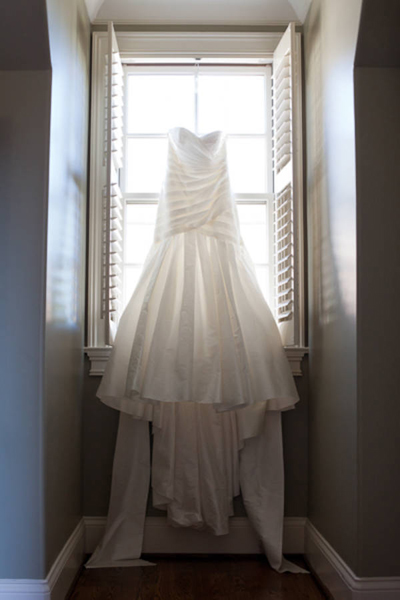 wedding gown hanging up in window