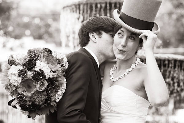 groom kissing bride wearing top hat