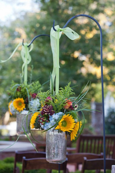 hanging flower arrangements lining outdoor wedding aisle