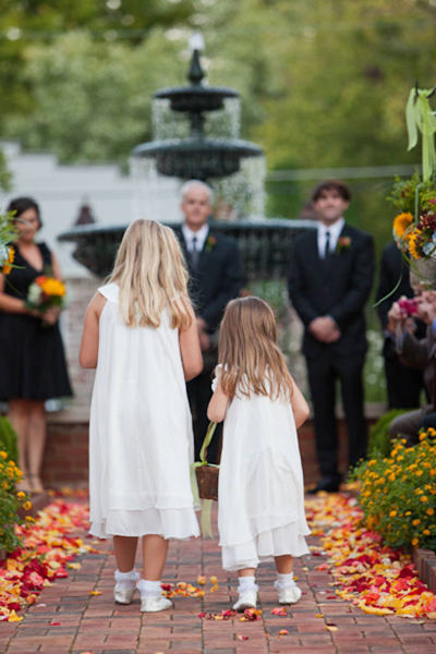 flower girls wearing white walking down aisle