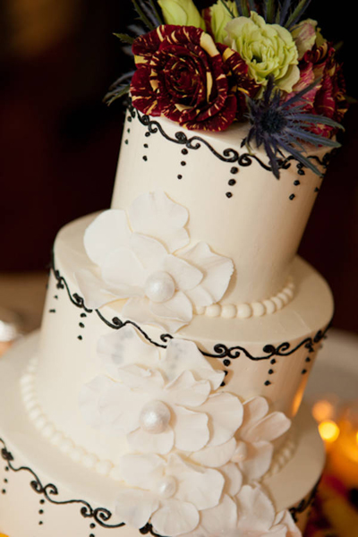 black and white wedding cake with flowers on top