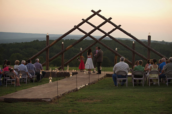 bride and groom at wooden outdoor wedding altar