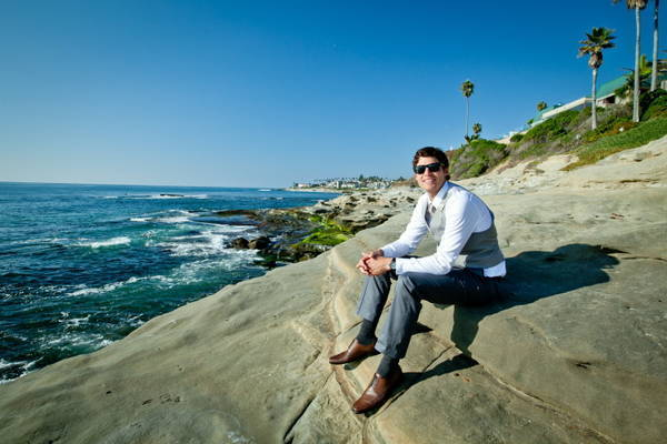 groom sitting by the ocean