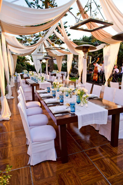 outdoor dining tables covered with draped fabric