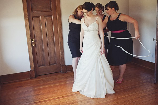 bridesmaids lacing up bride's dress