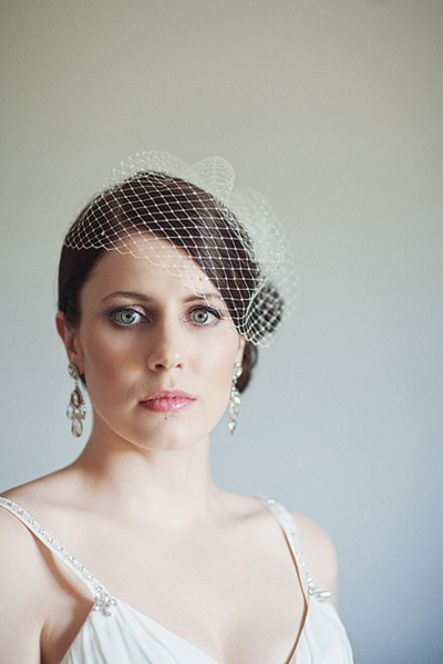 bride in birdcage veil and crystal chandelier earrings
