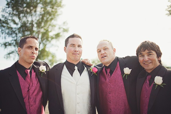 groom with groomsmen in black tuxedos with purple vests and ties