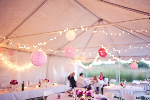 wedding reception tent with twinkle lights and pink paper lanterns