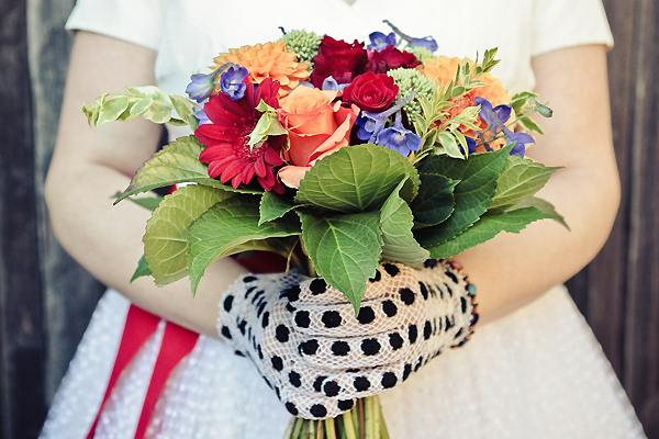 bride wearing black polka dot gloves holding multi-colored bouquet