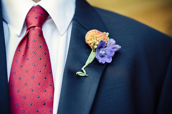 groom wearing orange and purple boutonniere