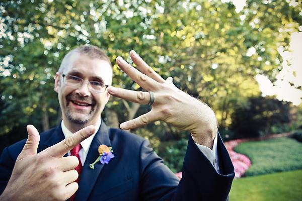 groom showing off his wedding ring