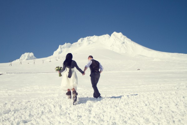 bride and groom running in the snow