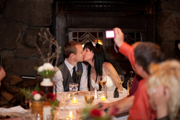 bride and groom kissing at the table