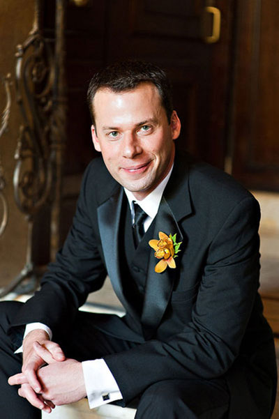 groom in black tuxedo with orange boutonniere