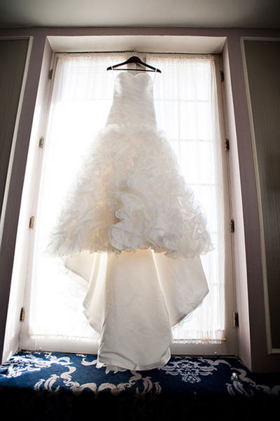 enzoani wedding gown hanging in window