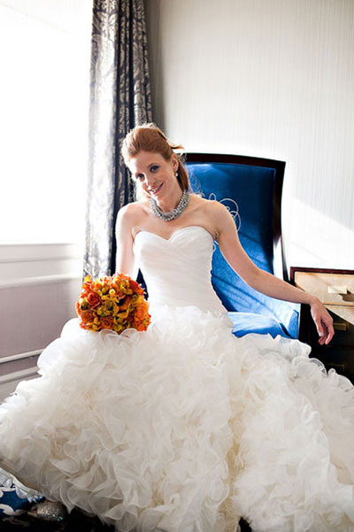 bride in enzoani gown with orange bouquet